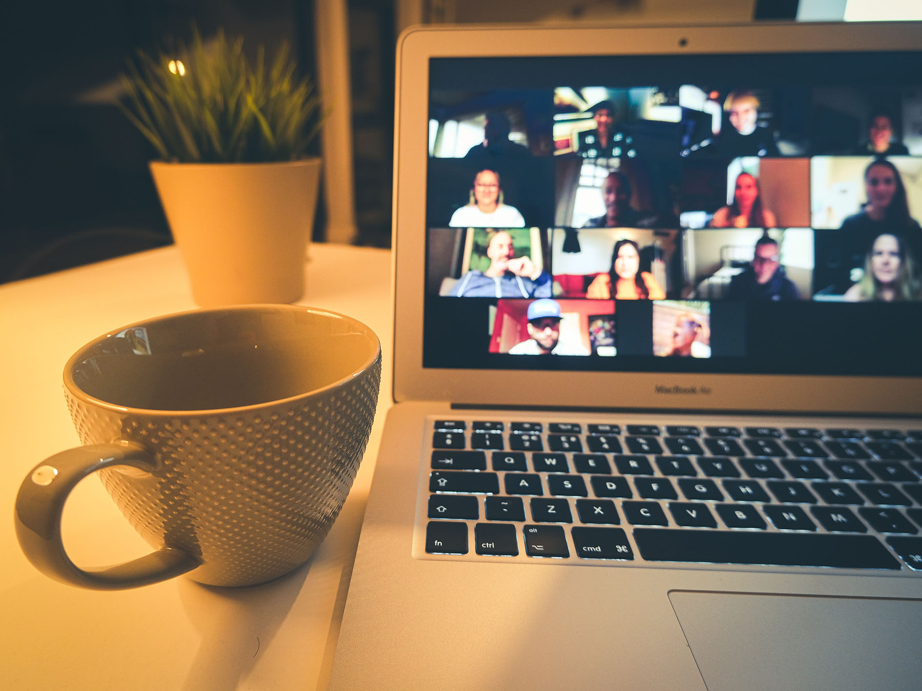 Photo of a cup of coffee sitting next to an engaging Zoom meeting on a laptop